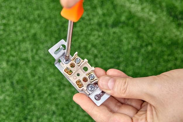 Eletricista solta o parafuso da tomada elétrica, close-up.