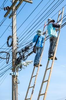 Eletricista subindo a escada de bambu para reparar fios elétricos.