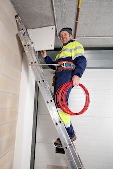 Eletricista subindo uma escada e olhando para a câmera