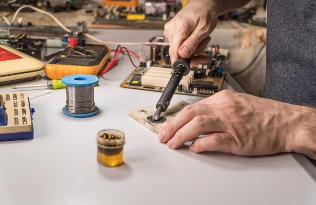 Eletricista técnico prepara ferro de solda de resina para funcionar