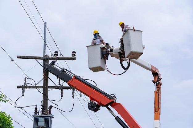 Eletricista trabalha em vagão de caçamba para manter linhas de transmissão de alta tensão.