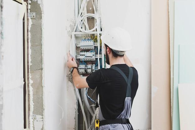 Eletricista trabalhando com fios na central telefônica