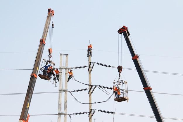 Eletricista trabalhando em altura por conectar um fio de alta tensão