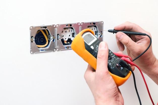 Eletricista uma tomada de parede com multímetro eletrônico. fio e multímetro em mãos fecham