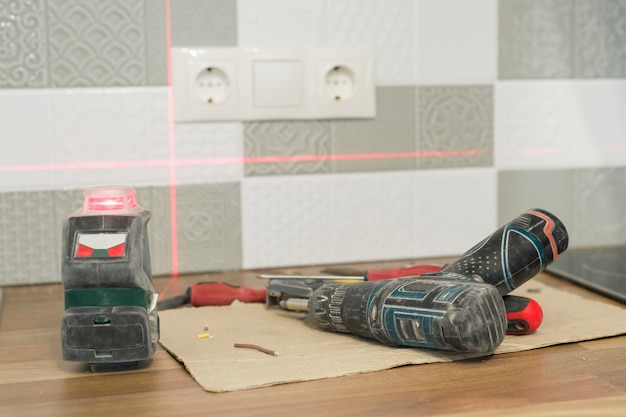 Eletricista usando nível de laser infravermelho para instalar tomadas elétricas