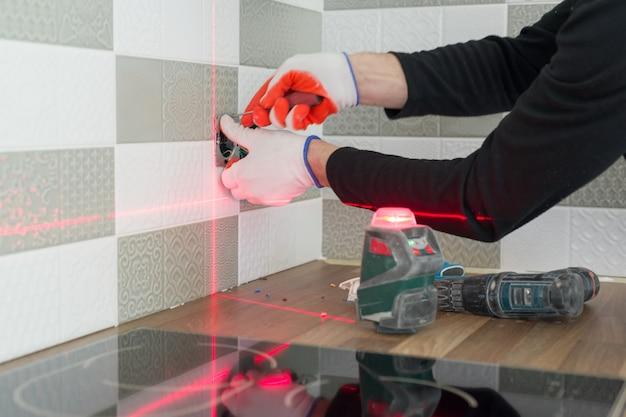 Eletricista usando nível de laser infravermelho para instalar tomadas elétricas.