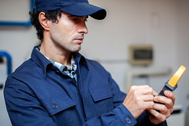 Eletricista usando um testador enquanto trabalhava na casa de um cliente
