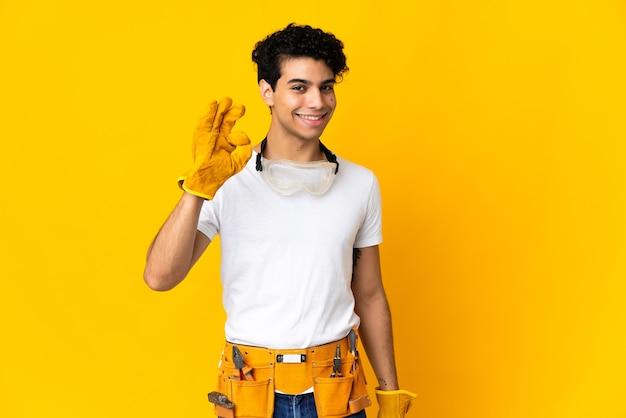 Eletricista venezuelano isolado em fundo amarelo mostrando sinal de ok com os dedos
