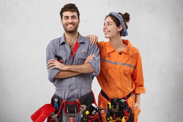 Eletricistas sorridentes e felizes usam uniforme e têm uma expressão alegre.