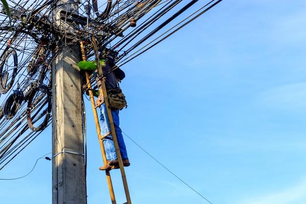 Eletricistas substituindo a alta tensão do cabo de alimentação