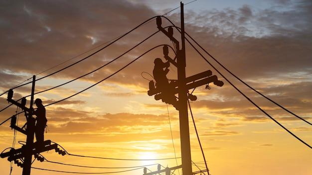 Eletricistas trabalham em torres de alta tensão para instalar novos fios e equipamentos.