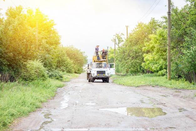 Eletricistas trabalhando em postes, um grupo de trabalhadores em veículos especiais