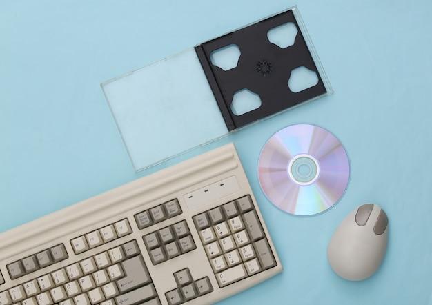 Eletrônica retro, tecnologia de pc dos anos 90. teclado de pc, mouse, cd em um fundo azul. vista do topo