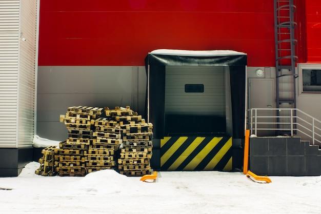 Elevador de carga para armazenamento com sinal de aviso de linhas diagonais pretas amarelas. paletes de madeira na neve. porta para carregamento automático de mercadorias com espaço de cópia. parede vermelha do armazém no inverno. edifício industrial close-up