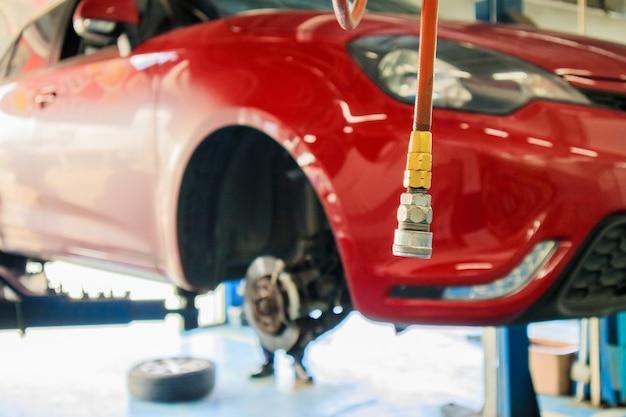Elevador de carro vermelho na estação de manutenção no centro de serviço automotivo desfocar o fundo abstrato