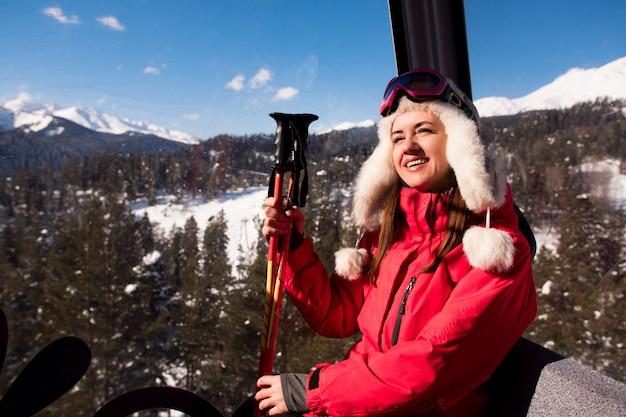 Elevador de esqui, esqui, estância de esqui - esquiador feliz no teleférico.