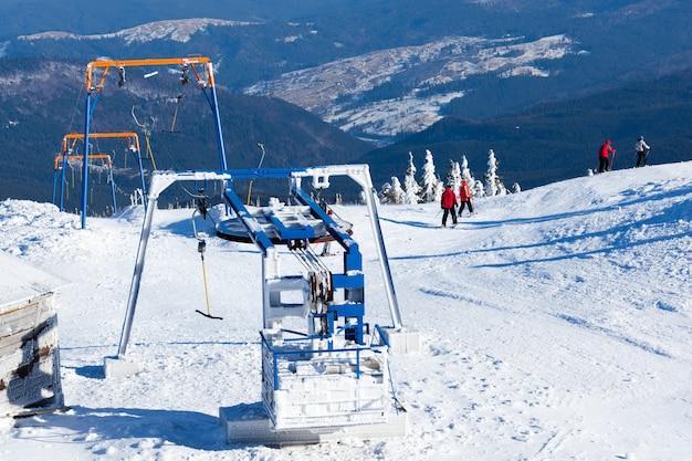 Elevador de esqui manual e alguns esquiadores com montanhas e vale ao fundo