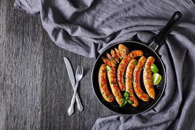 Elos originais de linguiça de porco ou hambúrgueres fritos em uma frigideira com manjericão fresco e cebolinha servidos em uma mesa de madeira escura com talheres, fatias de limão, vista de cima, disposição plana, cópia espaço Foto Premium