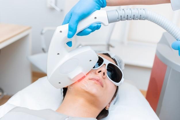 Elos procedimento de rejuvenescimento da pele facial de uma garota atraente close-up.