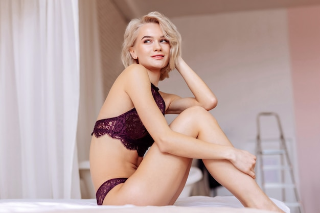 Em apartamento novo. jovem loira sexy sentada na cama no quarto do apartamento novo