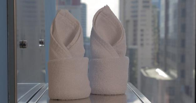 Em bangkok, tailândia, em uma sala em uma prateleira com um espelho colocado duas toalhas dobradas