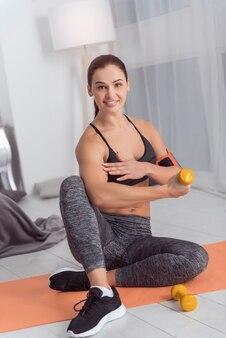 Em boa forma. linda alegre jovem atlética de cabelos escuros sorrindo e fazendo exercícios com pesos de mão enquanto está sentado no tapete em casa