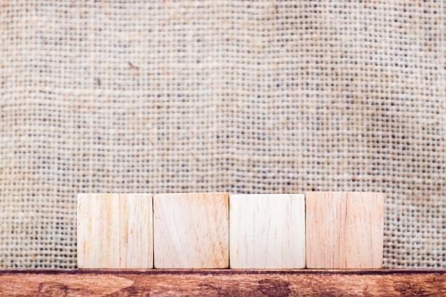 Em branco 4 pedaço de madeira de cubo na parede de tecido de madeira mesa e saco