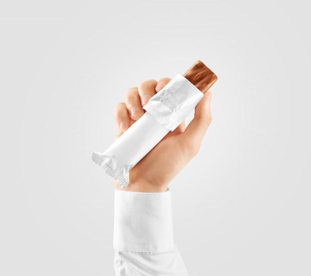 Em branco branco barra de chocolate envoltório plástico aberto segurar a mão