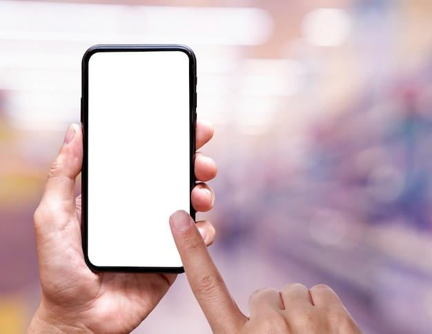 Em branco da tela do celular em mãos na loja de departamentos