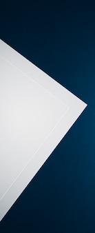 Em branco um papel branco sobre fundo azul como papelaria de escritório flatlay luxo branding flat lay e sutiã ...
