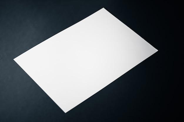 Em branco um papel branco sobre fundo preto como escritório papelaria flatlay luxo branding flat lay e br ...