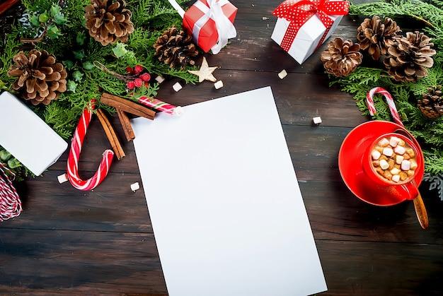Em branco vazio para escrever uma carta para o copo de cacau do papai noel com ramos de abeto de presente de marshmallows