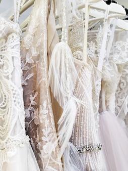 Em cabides brancos lindas roupas para a noiva no salão de casamento