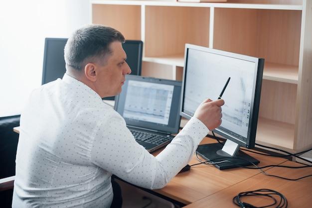 Em camisa branca oficial. o examinador de polígrafo trabalha no escritório com seu equipamento detector de mentiras