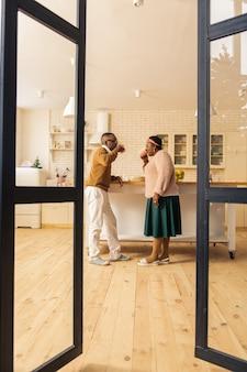 Em casa. belo casal feliz em pé juntos na cozinha enquanto bebem chá lá