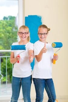 Em casa de família, menina com sua irmã ou amiga pintando com rolo de tinta uma parede em azul