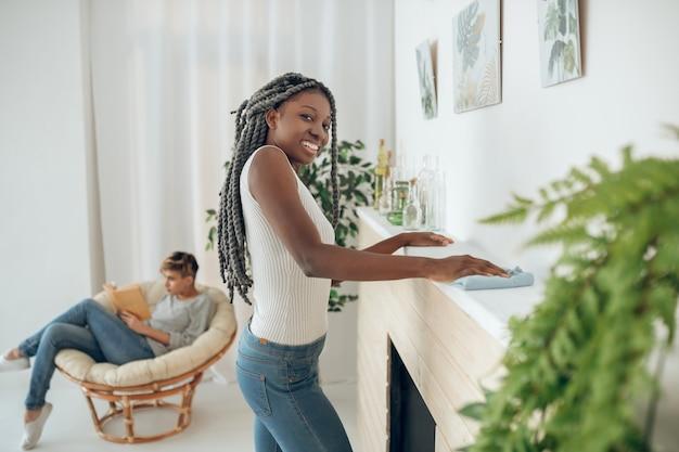 Em casa. garota de cabelos louros limpando o quarto, a namorada sentada na cadeira