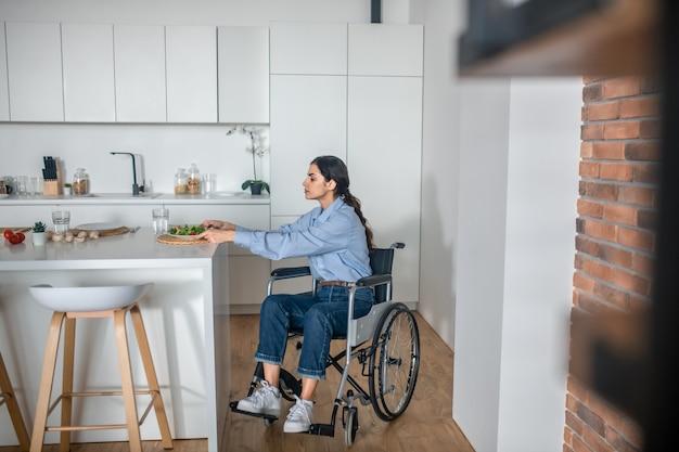 Em casa. uma linda garota em uma cadeira de rodas na cozinha de casa