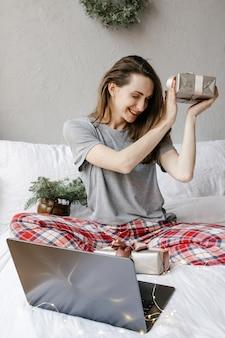 Em casa, uma mulher feliz está sentada em frente a uma tela de computador com uma caixa de presente nas mãos e mostra seu presente por meio de videochamada