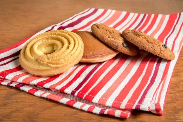 Em cima da mesa em uma toalha vermelha em bolos listrados é o café.