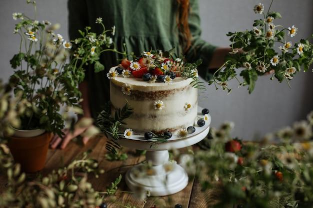 Em cima da mesa há um bolo decorado com frutas e flores