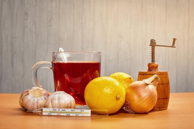 Em cima da mesa, uma caneca de chá com limão, cebola, alho e um termômetro