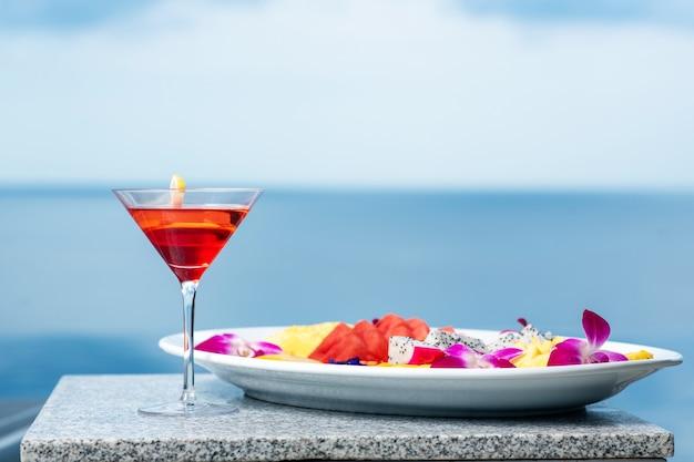 Em close o coquetel é cosmopolita com uma rodela de limão e ao lado um prato com frutas exóticas