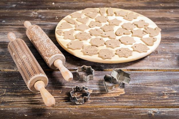 Em close-up em uma mesa de madeira, encontram-se lindos vários brinquedos para uma árvore de natal feita de argila marrom