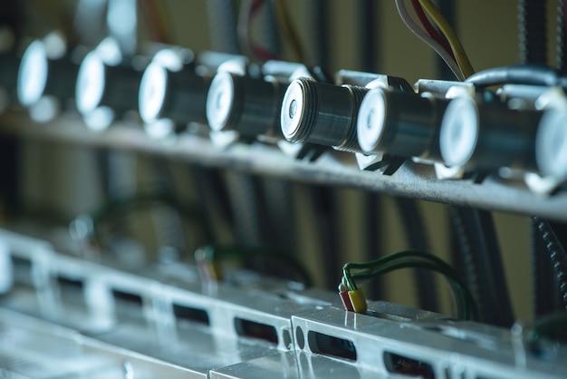 Em close-up, uma série de suportes de metal e fios pendurados conectados uns aos outros na produção de equipamentos militares sofisticados. conceito de manufatura industrial