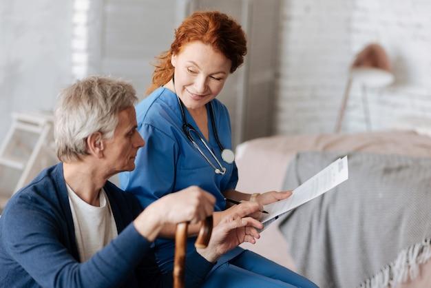 Em detalhes. senhora simpática, brilhante, confinada, mostrando alguns dados ao homem idoso e prescrevendo medicação especial para fazê-lo se sentir melhor