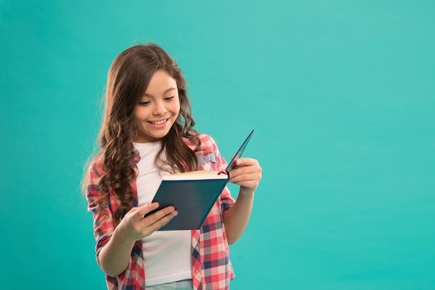 Em direção ao conhecimento. menina segura livro lido história sobre fundo azul. a criança gosta de estudar e ler um livro. conceito de livraria. livros infantis maravilhosos gratuitos disponíveis para leitura. literatura infantil.