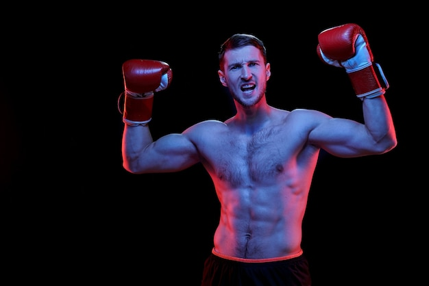 Em êxtase, jovem esportista musculoso sem camisa e usando luvas de boxe, levantando os braços enquanto grita contra a parede negra