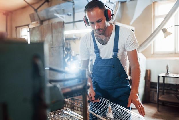 Em fone de ouvido de proteção silencioso. homem de uniforme trabalha na produção. tecnologia industrial moderna.