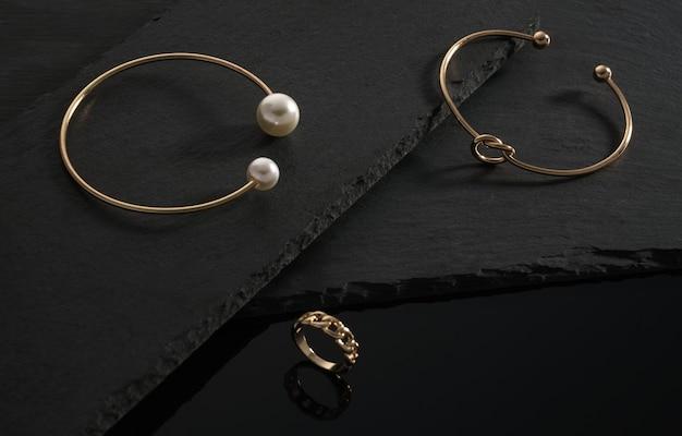 Em forma de nó e ouro com pulseiras de pérolas e anel em forma de corrente na superfície de pedra preta